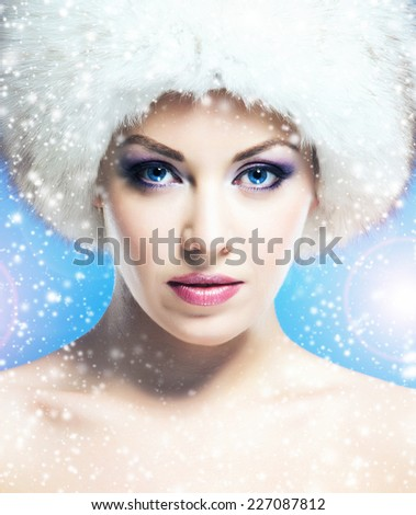 Portrait of young and beautiful woman in winter hat over blue background with a falling snowflakes - stock photo