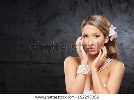 Portrait of young and beautiful woman wearing the pearl necklace and bracelet - stock photo