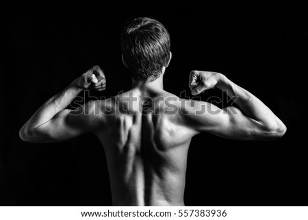 Portrait of young and fit male model posing his muscles in studio, back