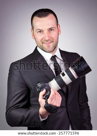 Portrait of young and handsome professional photographer in business suit, on grey vignetting background. - stock photo