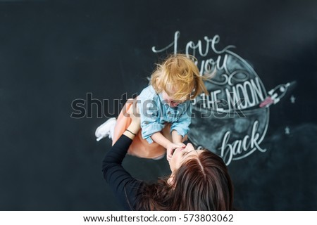 Portrait of young and happy mother with the little daughter against the background of the ornamented wall.