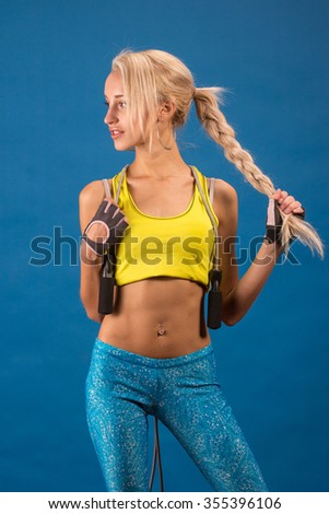 Portrait of young and healthy blonde with skipping rope over the blue background.