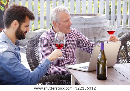 Portrait of young and senior man tasting with red wine in a vineyard. Professional winemakers sitting at desk in front of laptop at wine cellar and consulting. Small business.