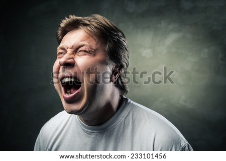 portrait of young angry man over dark grey background - stock photo
