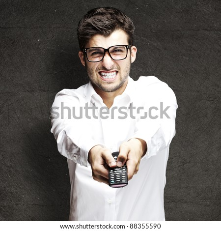 portrait of young angry man using remote control against a grunge background - stock photo