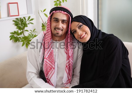 Portrait Of Young Arabic Couple Sitting On Sofa - stock photo