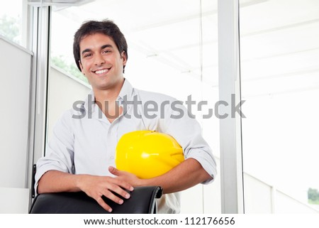 Portrait of young architect holding hard hat in office. - stock photo