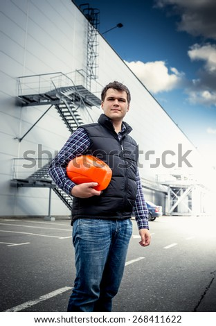Portrait of young architect posing with hardhat against industrial building - stock photo
