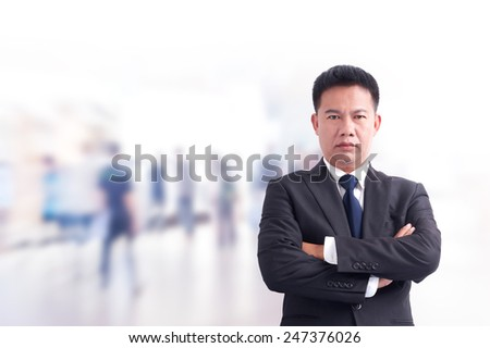 Portrait of young asia business man has office background .cross one's arm, - stock photo