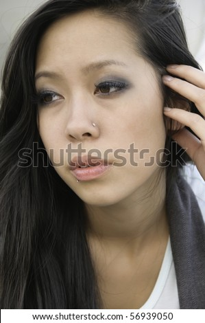 Portrait of young Asian-American woman with facial jewelry and long brunette hair
