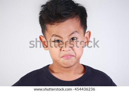 Portrait of young Asian boy getting angry and resentful - stock photo