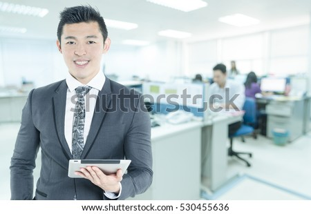 Portrait of young asian business man wear grey suit hold digital tablet in hand and look smile on his face in modern japan office with copy space area