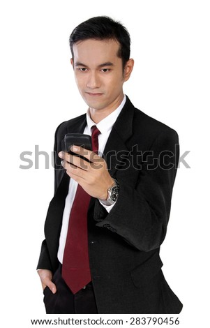 Portrait of young Asian businessman standing casually while checking on his mobile phone, isolated on white background - stock photo