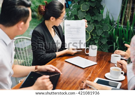 portrait of young asian businesswoman doing presentation while meeting in a cafe - stock photo