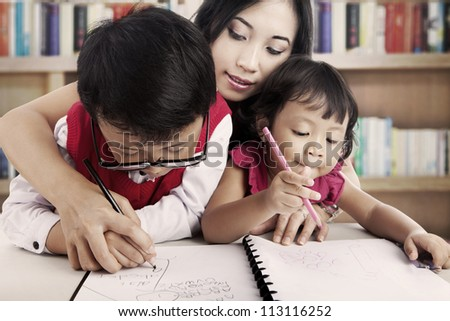 Portrait of young asian children write on the paper with their mother. shot in the library