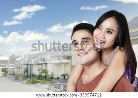 Portrait of young asian couple standing in front of new residential background - stock photo