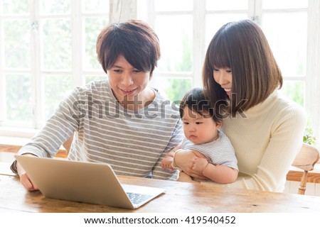 portrait of young asian family using laptop computer - stock photo
