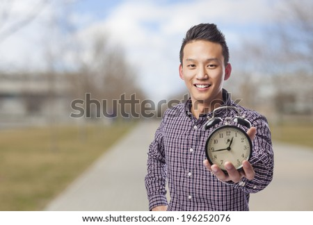 portrait of young asian man holding an alarm clock - stock photo