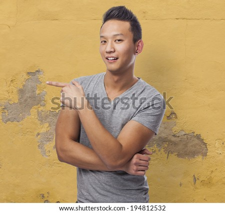 portrait of young asian man pointing with his finger - stock photo