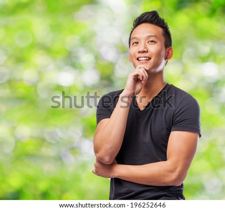 portrait of young asian man thinking at park - stock photo