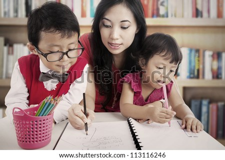 Portrait of young asian mother guiding her children to draw and write on the paper. shot in the library - stock photo