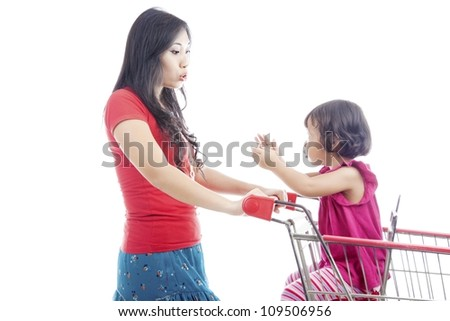 Portrait of young asian mother pushing a shopping cart and talking with her daughter on the shopping cart. - stock photo