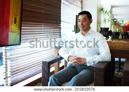 Portrait of young asian office worker dressed in corporate clothing enjoying free time while sitting in modern restaurant interior, smiling successful businessmen speaks with someone in office indoors