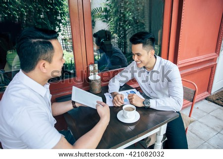 portrait of Young asian successful businessman and business partner with tablet in cafe - stock photo