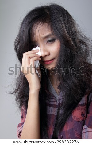 Portrait of young Asian woman crying, wipe her tears with tissue, on grey background - stock photo