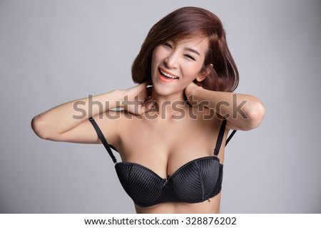 Portrait of young asian woman in sexy black bra or lingerie with big boobs laughing. - stock photo