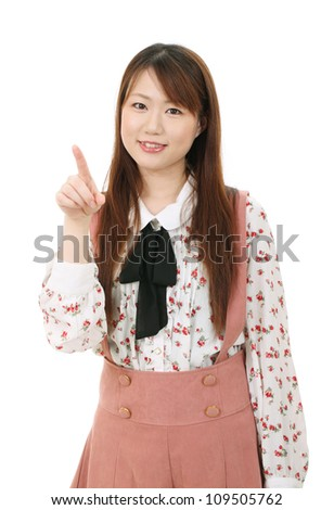 Portrait of young asian woman pointing - stock photo