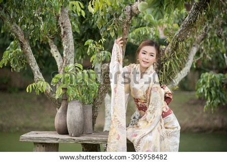 Portrait of young Asian woman wearing kimono and fresh green leaves - stock photo