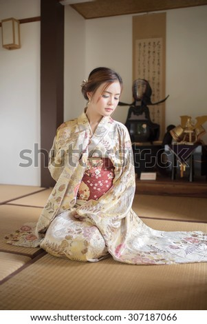 Portrait of young Asian woman wearing kimono and Japanese-style room - stock photo