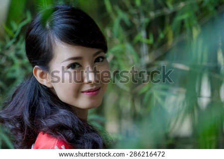Portrait of young Asian woman wearing kimono in the park - stock photo