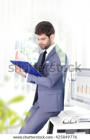 Portrait of young assistant businessman doing some paperwork while standing at his workplace at bank.