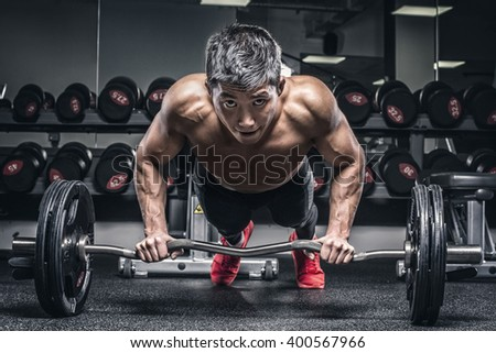 portrait of young athlete pushing up against barbell - stock photo