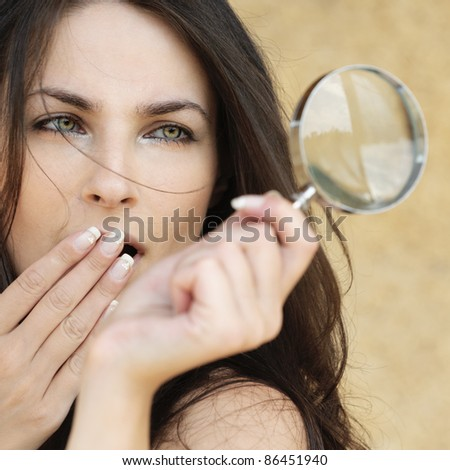 Portrait of young attractive amazed woman holding loupe and covering her mouth with hand against yellow background. - stock photo