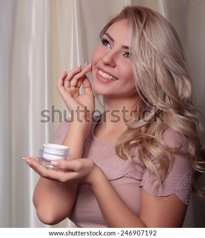 Portrait of young attractive blonde woman with a jar of cream in his hand, which put the cream on face. Beauty, grooming and health - stock photo