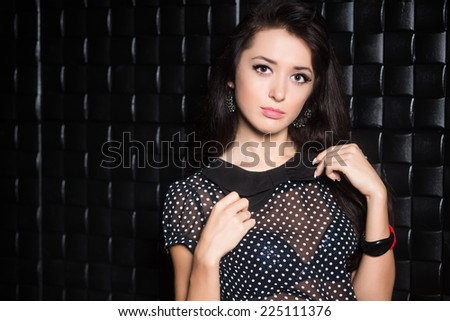 Portrait of young attractive brunette posing near a black wall - stock photo