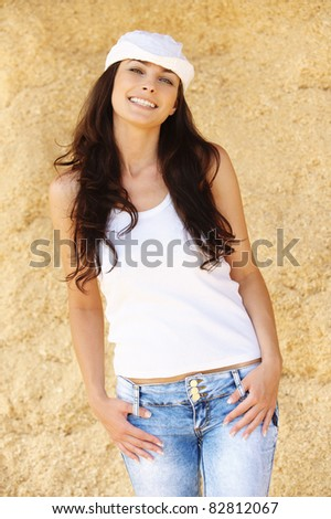 Portrait of young attractive brunette woman wearing white cap, t-shirt and jeans, standing against beige background. - stock photo
