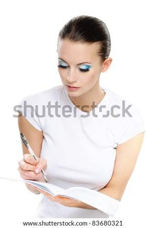 Portrait of young attractive brunette woman wearing white t-shirt and writing something against white background. - stock photo