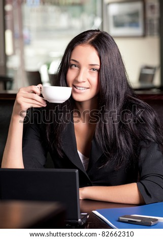 Portrait of young attractive business woman drinking coffee and using laptop
