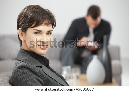 Portrait of young attractive businesswoman sitting at office lobby, smiling.