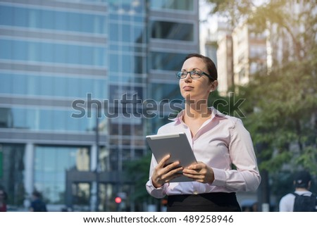 Portrait of young attractive businesswoman with modern tablet outdoors, close-up of smiling businesswoman in white shirt outdoors near her office, Woman working outdoor, sunny day, blurred background