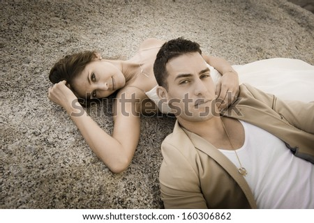 Portrait of young attractive caucasian couple leaning against rock on beach at sunrise - stock photo
