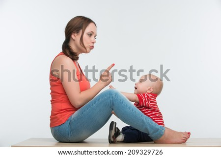 Portrait of young attractive Caucasian mother sitting face to face to her cute naughty toddler son, lifestyle upbringing concept, isolated on white - stock photo