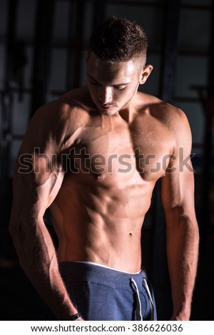 Portrait of young attractive caucasian muscular bodybuilder man with perfect body working out in gym, posing, showing abdominal and arm muscles, body sculpture concept - stock photo