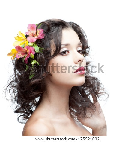 portrait of young attractive caucasian woman with lily flowers in hair isolated on white