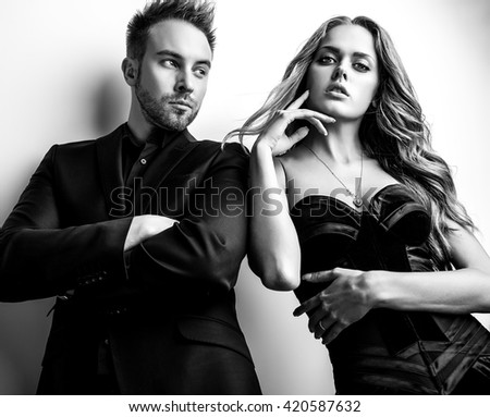 Portrait of young attractive couple posing studio dressed in black fashionable clothes. Black-white photo. - stock photo