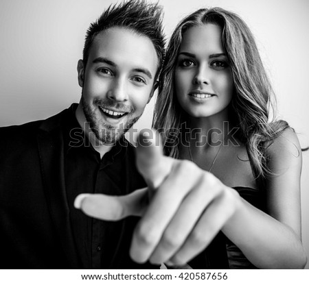 Portrait of young attractive couple posing studio dressed in black fashionable clothes. Black-white photo.